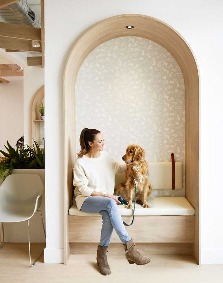 Woman sitting with dog inside Small Door Vet